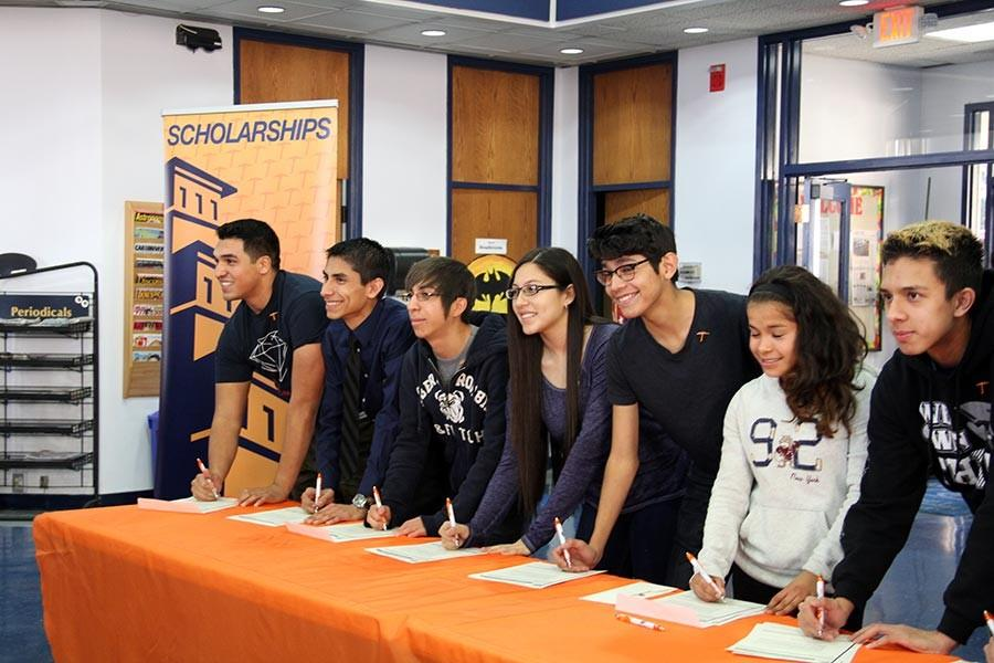 Students get ready to sign their contract and accept the scholarships.