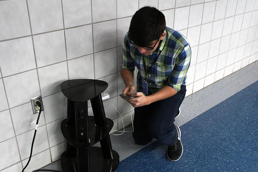 Junior student Bryan using new charging post provided by the school