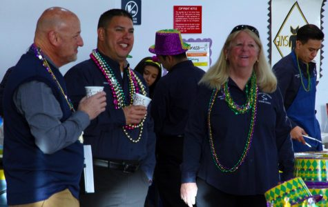 Student council sponsor Cindy Spitz enjoys the Leadership meeting celebrating Mardi Gras Feb. 13, with Chris Lopez and Coach Bruce Reichman.