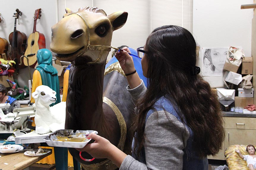 Sophomore Nailea touches up the last details during restoration of a Nativity Scene figure, Oct. 30