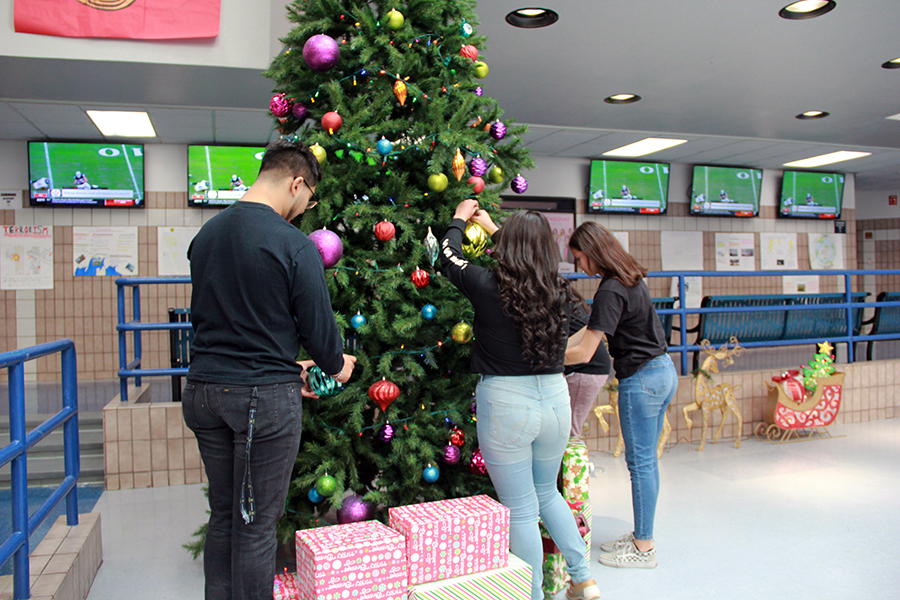 Student Council adds the finishing touches to the Christmas tree in the commons, Dec. 10.