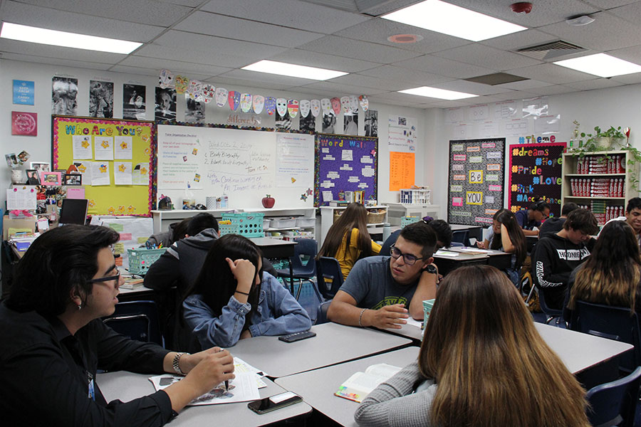 Juniors Danielle Garcia, Nicole Gongora, Ramon Urueta and Christian Valencia discuss the  class reading assignment in AP teacher Andrea Morse's English III, Oct. 2.