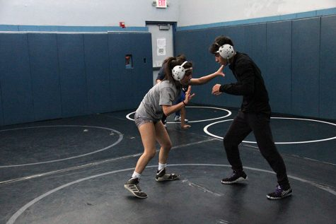 Varsity wrestling team members Annahi Duchene and Diego Estala  practicing techniques after school.