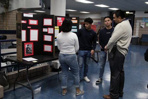 Assistant principal Victor Lara judges at the science fair.