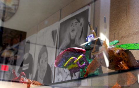 Alebrijes and charcoal self-portraits displayed in the Fine Arts Hall building.