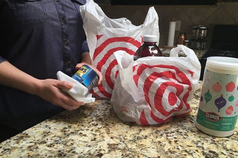 A customer from Target disinfects her groceries after leaving the store.