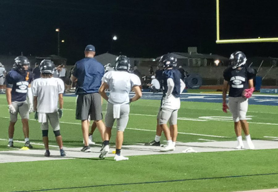 Varsity football coach Contrerass with wide varsity receivers at Midnight Madness practice, August 14.