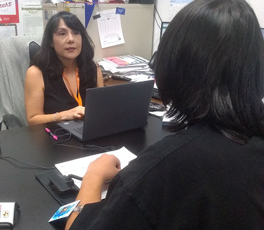 Go Center counselor  Julie Rodriguez helps a student with his application.